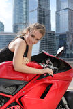 Biker girl sitting on her bike on urban background Royalty Free Stock Image