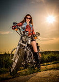 Biker girl sitting on motorcycle. Biker girl with sunglasses sitting on motorcycle Stock Photo