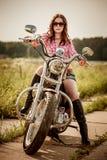 Biker girl sitting on motorcycle. Biker girl with sunglasses sitting on motorcycle Royalty Free Stock Images