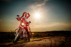 Biker girl sitting on motorcycle Stock Photo