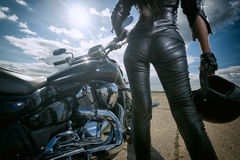 Biker girl standing by a motorcycle. Royalty Free Stock Photo
