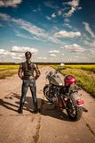 Biker girl. Stands on the road and looks into the distance Stock Images