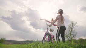 Biker-girl at the sunset on the meadow. Child enjoying freedom on bike on wheat field at sunset. Girl on a bike in the