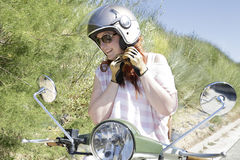 Biker girl trying on a motorcycle helmet Royalty Free Stock Photos