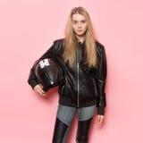 Biker girl wearing black leather jacket holding motorcycle helmet.  Royalty Free Stock Image