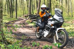 Biker girl wearing a motorcycle outfit, protective clothing, equipment, adventure touristic motorbike with side bags. outdoor royalty free stock images