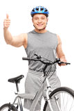 Biker giving thumb up and posing with a bicycle Stock Photography