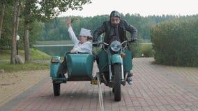 Biker in glasses ride motorcycle with woman nurse costume grimacing in sidecar stock video footage