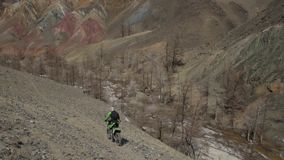 The biker goes through the montain valley on the speedy motorcycle. The road is gravel and sandy and goes on the slope of the hill with the wild river at the stock video footage
