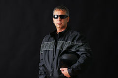 Biker guy with sunglasses. Tough looking guy with biker jacket and helmet, could be criminal, middle aged, studio shot over black Stock Photography