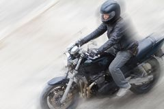 Biker in helmet and black jacket riding on the road. Royalty Free Stock Image