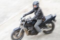 Biker in helmet and black jacket riding on the road. Royalty Free Stock Photo