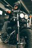 Biker in helmet and his style motorcycle on a city streets Royalty Free Stock Photo