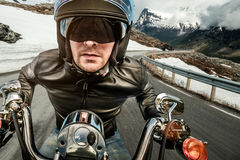 Biker in helmet and leather jacket racing on mountain serpentine Royalty Free Stock Photography