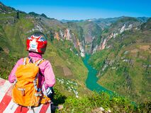 Biker with helmet looking at view Ha Giang karst geopark mountain landscape in North Vietnam. Unique canyon with blue river. Ha
