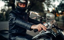 Biker in helmet poses on classical chopper royalty free stock photography