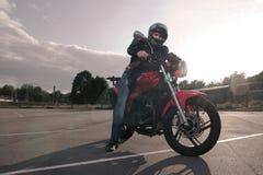 Biker in helmet posing. On motorbike Royalty Free Stock Photography