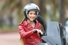 Biker on her motorbike looking at camera. Happy biker wearing an helmet sitting on her motorbike looking at camera on the street Royalty Free Stock Photos