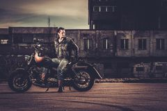 Biker and his bobber style motorcycle. On a city streets stock photo