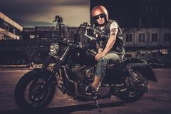 Biker and his bobber style motorcycle. On a city streets royalty free stock photo