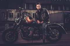 Biker and his bobber style motorcycle. On a city streets royalty free stock photos