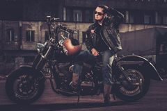Biker and his bobber style motorcycle. On a city streets stock images
