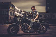 Biker and his bobber style motorcycle. On a city streets royalty free stock images