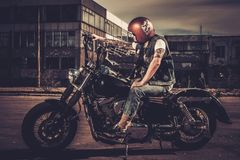 Biker and his bobber style motorcycle. On a city streets stock image
