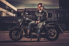 Biker and his bobber style motorcycle Royalty Free Stock Photo