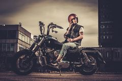 Biker and his bobber style motorcycle. On a city streets stock photography