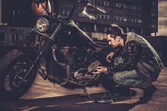 Biker and his bobber style motorcycle. Biker repairing his custom motorcycle bobber on a road stock photos