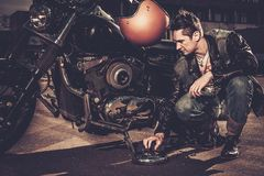 Biker and his bobber style motorcycle. Biker repairing his custom motorcycle bobber on a road royalty free stock photos