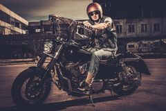Biker and his bobber style motorcycle. Tattooed biker and his bobber style motorcycle on a city streets royalty free stock photo