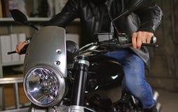 Biker on his motorcycle in a garage. A biker on his motorcycle in a garage stock image