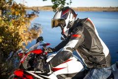Biker in a helmet sitting on a sports bike near the lake stock photo