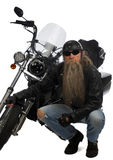 Biker and his trusty ride. On white an older man with a long beard wearing a leather jacket, motorcycle helmet and sun glasses checking out his front tire on Stock Image