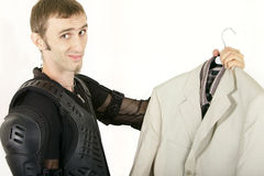 Biker holding a business suit. Biker not considering a suit as his new image Stock Photo