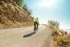 Biker hot sun uphill yellow jacket Royalty Free Stock Photo