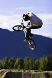 Biker jump sequence. A bmx rider does a big trick off a dirt jump Royalty Free Stock Images