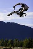 Biker jump sequence. A bmx rider does a big trick off a dirt jump Stock Photos