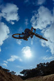 Biker jumping against sun Stock Image