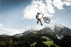 Biker jumps a high stunt. With mountains in the back stock photos
