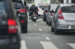 Biker in between lanes. Motorcyclist in between lanes passing cars royalty free stock photography