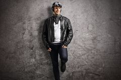Biker leaning against a rusty gray wall Stock Photos