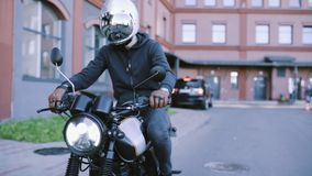 Biker in leather gloves and black hoodie starts motorcycle