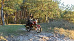 Biker in a leather jacket and helmet on a retro motorcycle in the forest stock photography