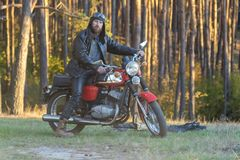 Biker in a leather jacket and helmet on a retro motorcycle in the forest royalty free stock photography