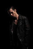 Biker in leather jacket posing with hands in pockets. Handsome biker in black leather jacket posing in dark studio background with hands in pockets looking at Stock Images