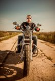 Biker in a leather jacket riding a motorcycle on the road stock photography