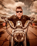 Biker in a leather jacket riding a motorcycle on the road Royalty Free Stock Images